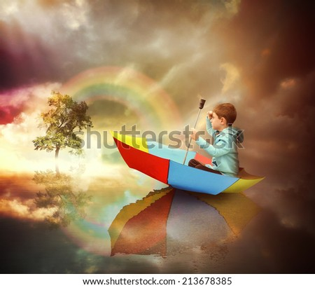 A little child is sitting in an umbrella boat looking at a distant tree of light with a rainbow for an imagination or freedom concept. - stock photo