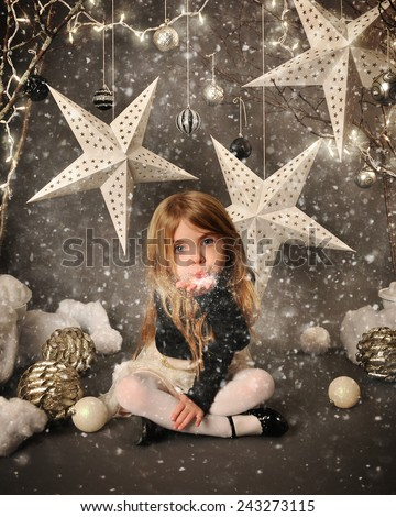 A little child is sitting on a winter wonderland backdrop with trees and white stars. She is blowing snow in her hand for a season or holiday concept. - stock photo
