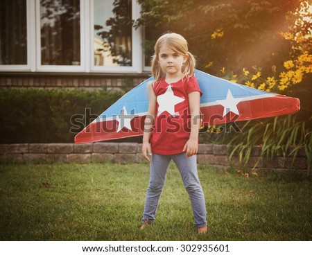 A little child is wearing homemade cardboard flying wings with stars on them pretending to be a pilot for a craft, imagination or exploration concept. - stock photo