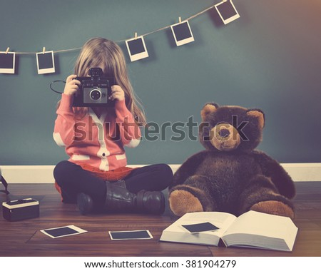 A little child photographer is taking a photo with her teddy bear and film prints on the ground for a art or creativity concept. - stock photo