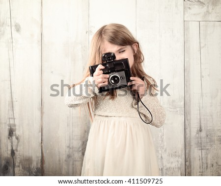 A little child photographer is taking a photo with with an old film camera against a white wood wall for an art or creativity concept. - stock photo
