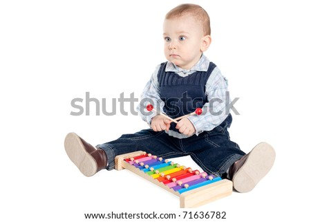a little child playing on xylophone
