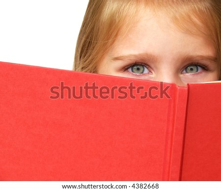 a little child's eyes looking over the top of a book - stock photo