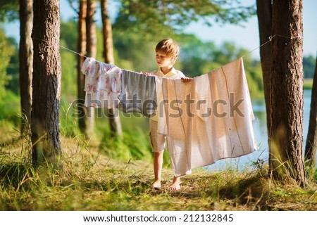A little cute boy hanging washing on a line in a pine forest on the bank of a lake in a sunny summer day. Kids are playing. - stock photo