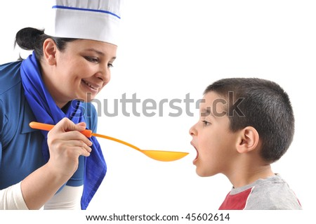 A little cute boy tasting the food prepared by female cook. White background studio image - stock photo
