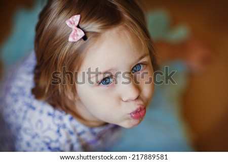 A little cute girl blowing kisses close up. - stock photo