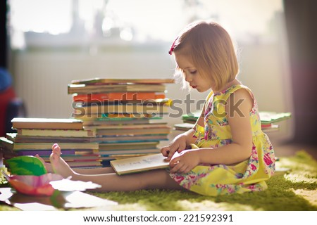 A little cute girl in a yellow dress reading a book sitting on the floor - stock photo