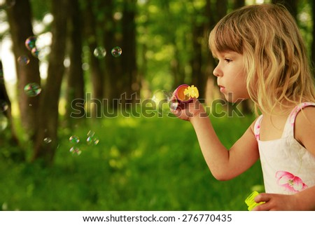 a little cute girl with soap bubbles - stock photo