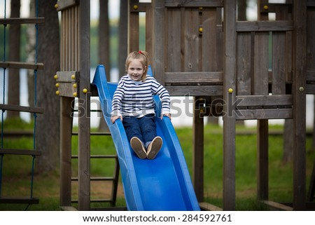 A little cute smiling girl in a striped pullover playing on a children's wooden playground on a sunny spring day  - stock photo