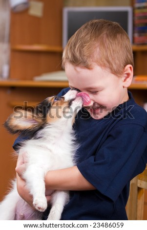 A little dog licking a young boy's nose - stock photo