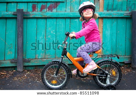 A little dreamy girl in pink glasses riding a bicycle in slums - stock photo