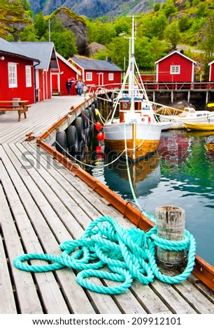A little fishing village with a boat and typical houses in a harbor on Lofoten islands, Norway - stock photo