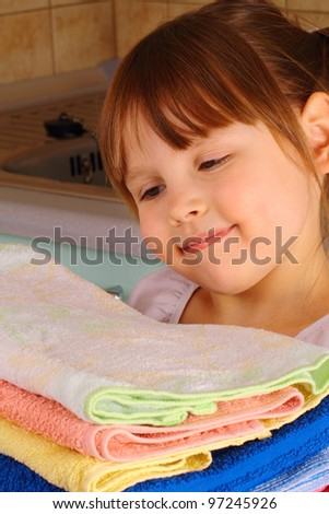A little girl admires the towels after washing - stock photo