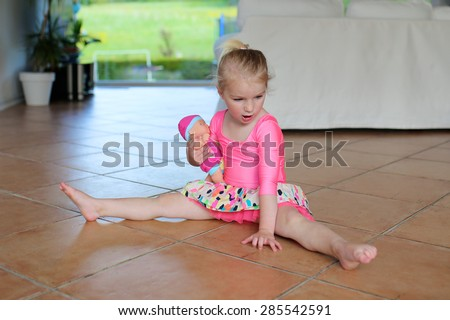 A little girl, adorable young talented dancer does ballet poses and stretching exercises on the floor at home - stock photo