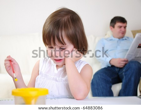 A little girl alone draws on the album. - stock photo