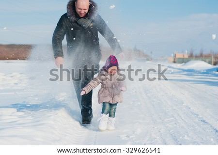 A little girl and dad run and play with the snow, lifestyle, winter holidays