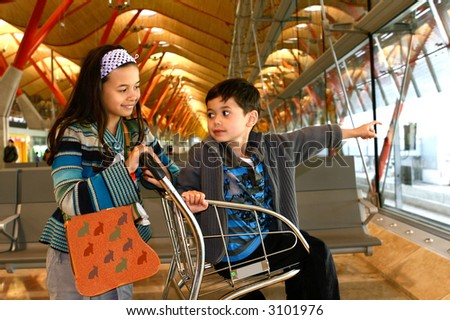 A little girl and her brother awaits for their flight departure at the departure lounge of an airport. - stock photo