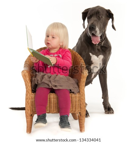 A little girl and her dog are reading a book - stock photo