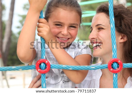 a little girl and her mother playing in a playground - stock photo