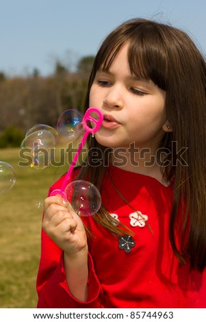 A little girl blowing bubbles on a warm summer day - stock photo