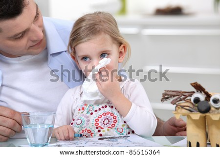 A little girl blowing her noise. - stock photo