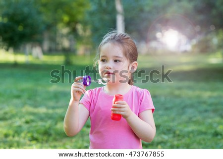 A little girl blowing soap bubbles in a park