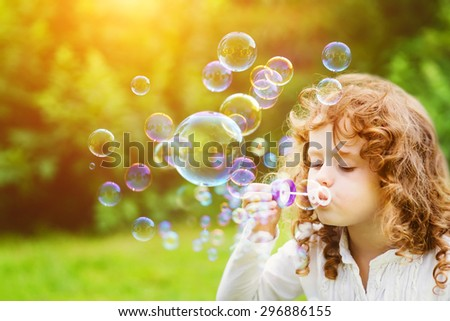 A little girl blowing soap bubbles in summer park. Background toninf for instagram filter. - stock photo