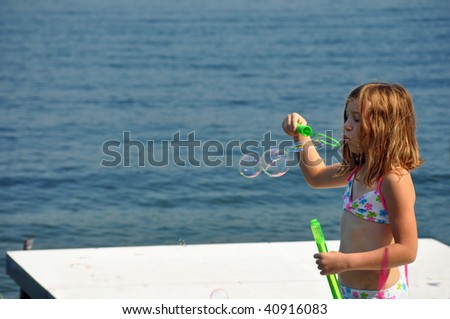 a little girl blows bubbles at the lake on a summer day - stock photo