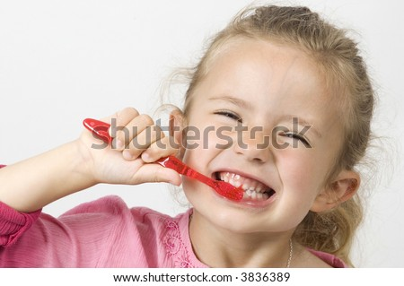 A little girl brushing her teeth with a brightly coloured toothbrush - stock photo