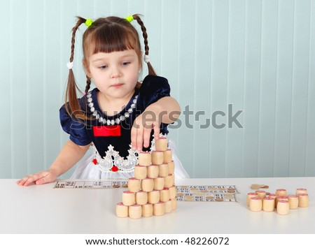 A little girl builds a tower of lotto sitting at the table - stock photo