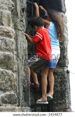 A little girl climbs on the gate, spurring her little brother along as well Concept: Together we succeed - stock photo