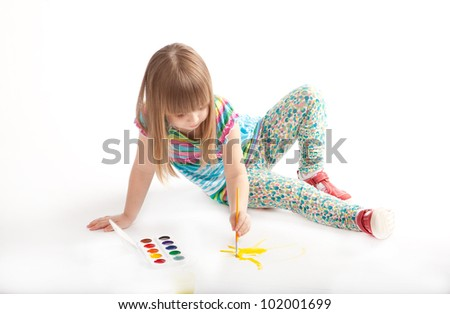 a little girl drawing on the floor in the studio - stock photo