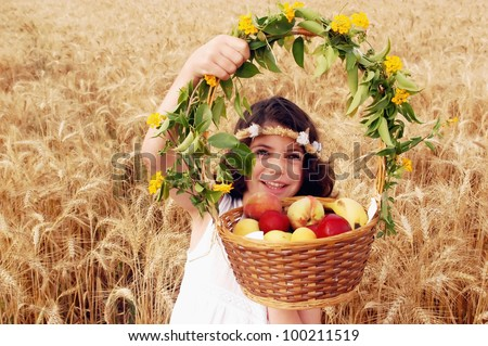 A little girl dressed in white holds a basket full of fresh fruit in a wheat field. - stock photo