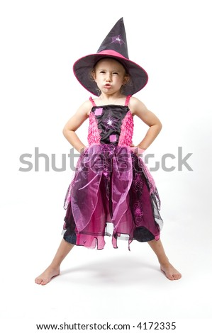 A little girl dressed up as a witch pulls a face - stock photo