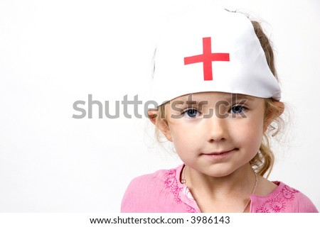 A little girl dresses up as a nurse against a white background - stock photo