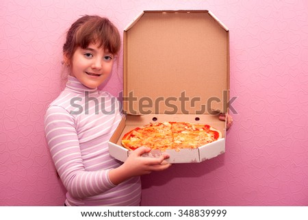 a little girl eating a pizza - stock photo