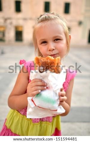 a little girl eating baguette sandwich - stock photo