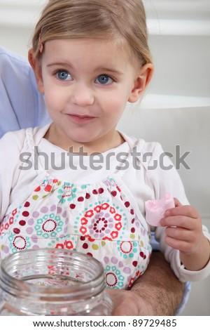 A little girl eating marshmallows. - stock photo