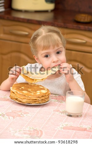 A little girl eats pancakes - stock photo