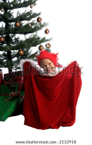 A little girl elf with a big smile in Santa's bag under the Christmas Tree