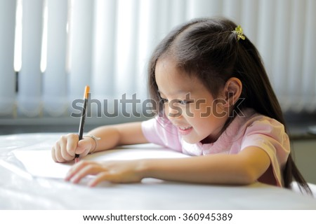 A little girl enjoying her learning at school - shallow depth of field focusing on her left eye - copy space available - stock photo