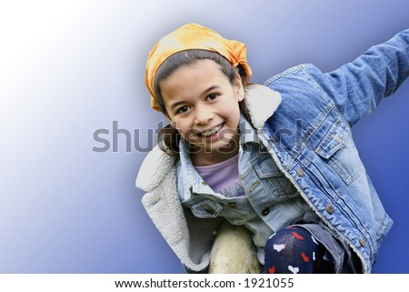 A little girl enjoying the outdoors, with blue background. - stock photo
