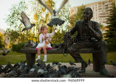 a little girl feeding the pigeons in the park near the statue - stock photo