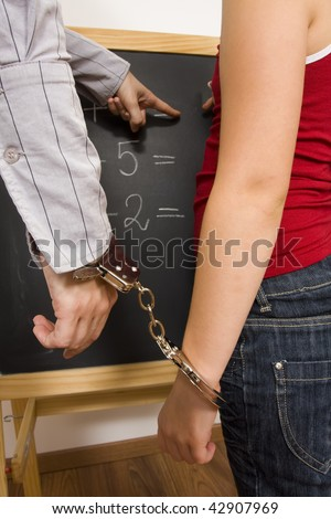 A little girl fettered with a handcuff to her teacher in the front of a blackboard. - stock photo