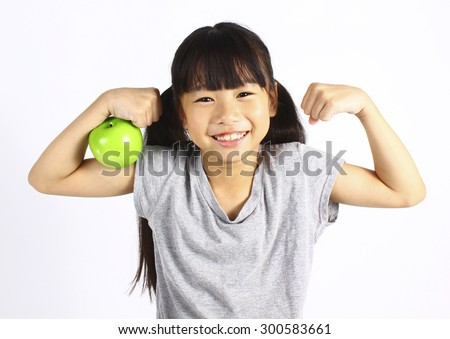 A little girl flexes her muscle while showing off the apple that made her strong and healthy  - stock photo