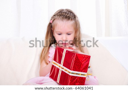A little girl give a holiday gift in red box with white ribbon.