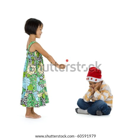 a little girl giving her friend a lollipop for christmas. they boy doesn't appreciate it at all. isolate on white background. - stock photo