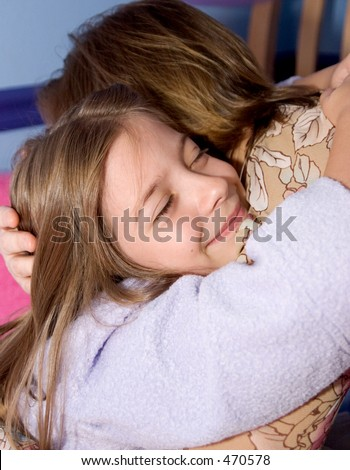 A little girl giving her mother a goodnight hug