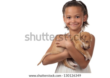 A little girl happily cuddles her little puppy. - stock photo