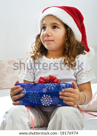 a little girl happy after receiving a Christmas present - stock photo